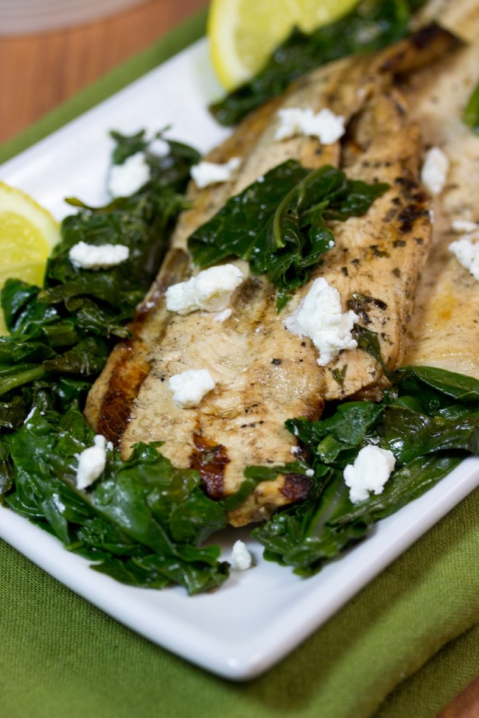 close up of grilled chicken topped with goat cheese