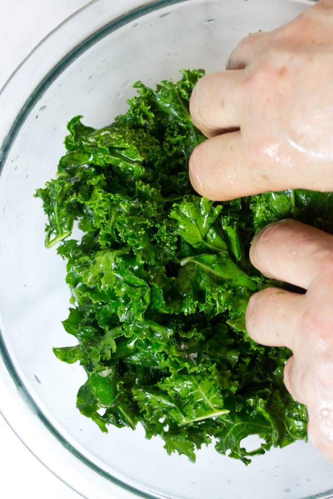 woman's hands massaging kale in a glass bowl