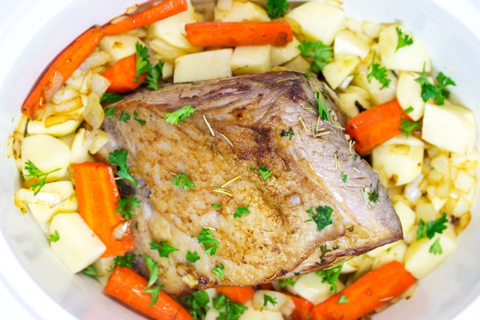 meat in a slow cooker surrounded by veggies