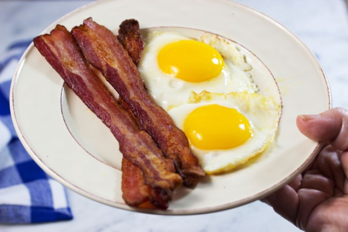 woman serving delicious bacon cooked in the oven with sunny side up eggs