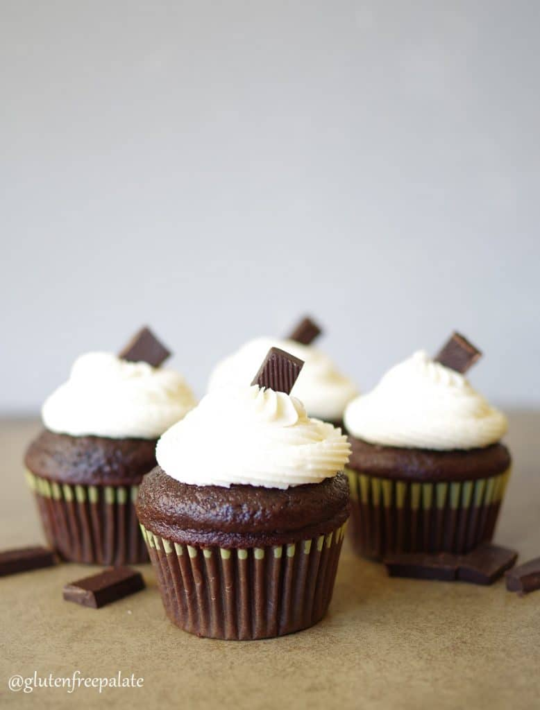 four Gluten Free Vegan Chocolate cupcakes topped with a white buttercream frosting and a piece of chocolate