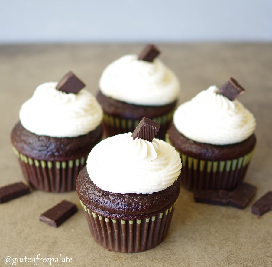 four Gluten Free Vegan Chocolate cupcakes with white buttercream frosting topped with a piece of chocolate