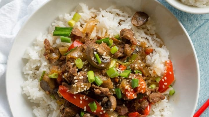 a close up of Mongolian beef and vegetables over rice in a white bowl with red chop sticks on the side