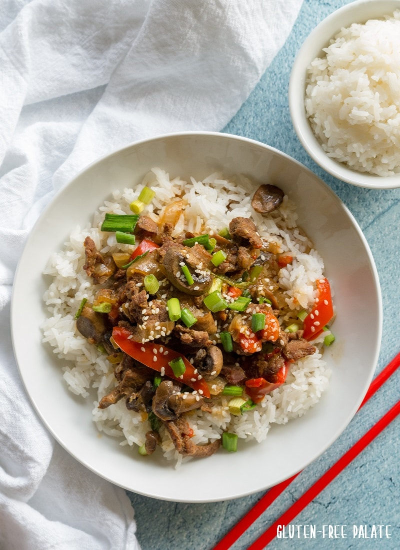 Mongolian beef and vegetables over rice in a white bowl with red chop sticks on the side