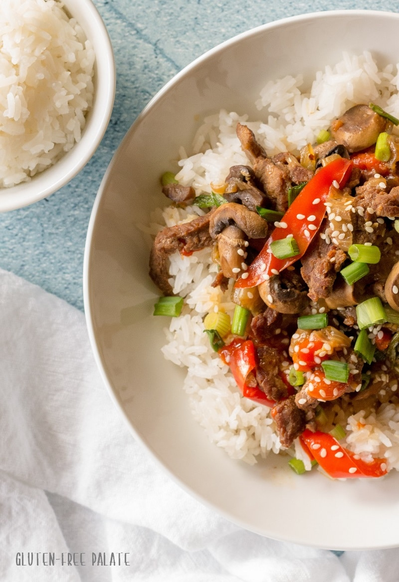 a close up of the side of Mongolian beef and vegetables over rice in a white bowl