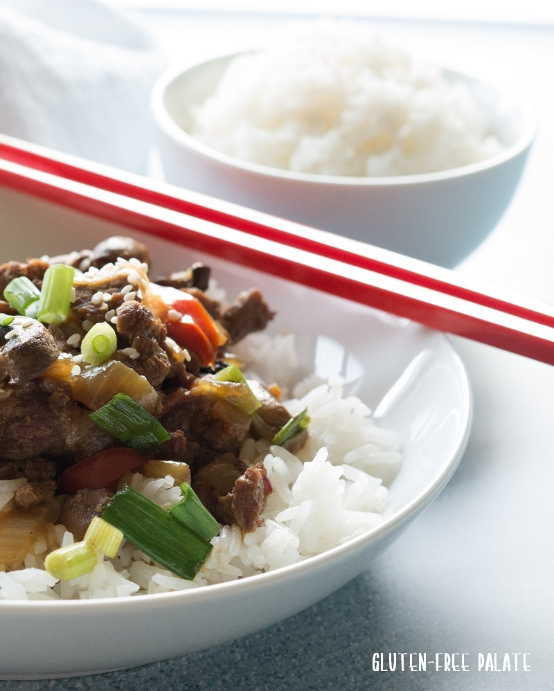 a front close up view of Mongolian beef and vegetables over rice in a white bowl with red chop sticks resting on the side of the bowl