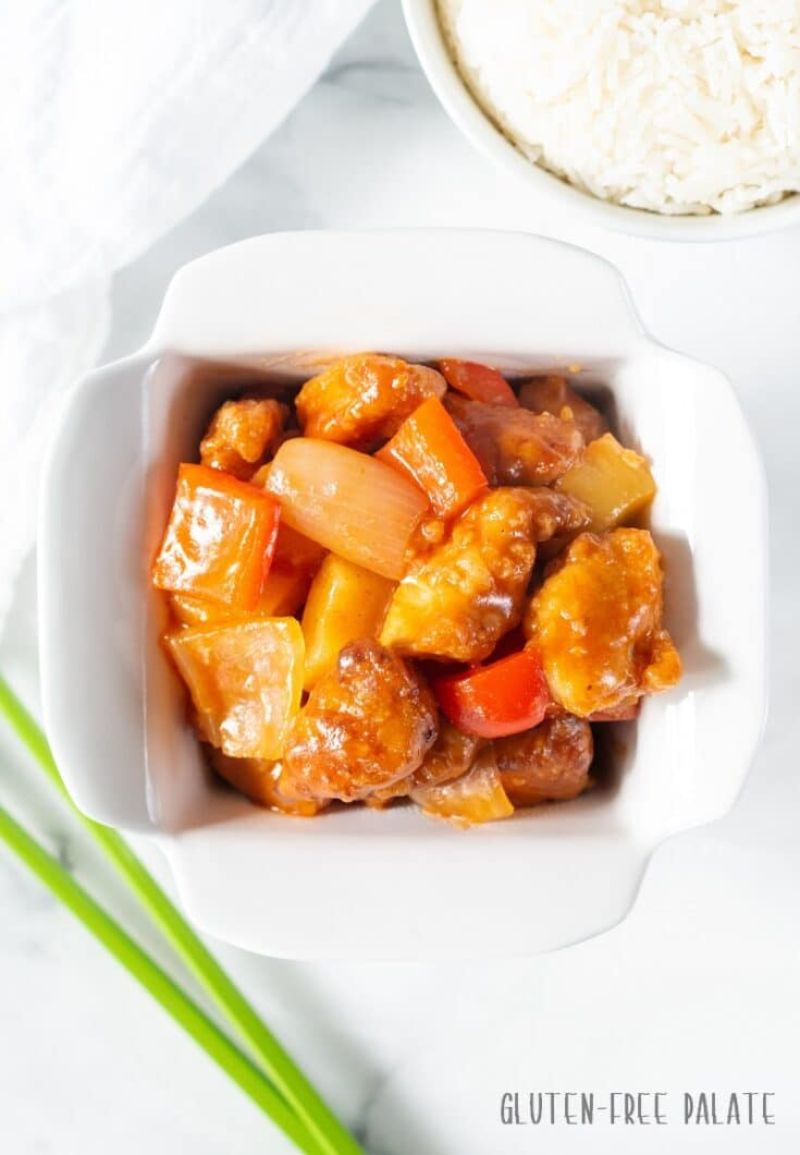Gluten Free Sweet and Sour Chicken in a white dish with a spring of onion next to it