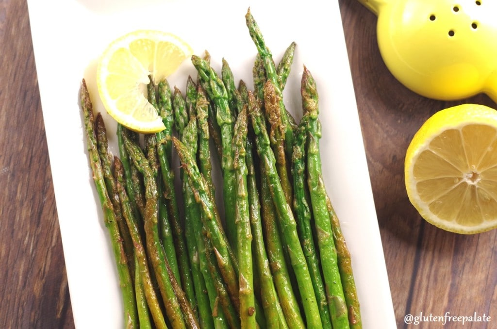 Asparagus spears on a white plate with a slice of lemon, with a wedge of lemon on the side