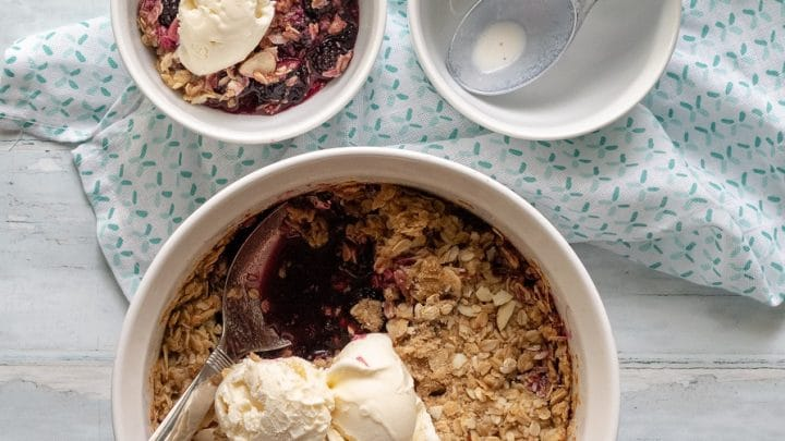 a close up of blackberry crisp topped with two scoops of vanilla ice cream, next to a bowl of blackberry crisp and a ice cream scoop