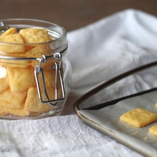 a close up of gluten free cheese crackers in a clear jar next to a baking sheet with crackers