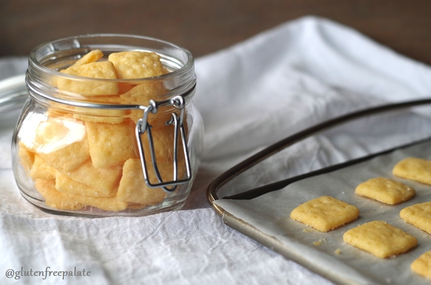 gluten free cheese crackers in a clear jar next to a baking sheet with crackers