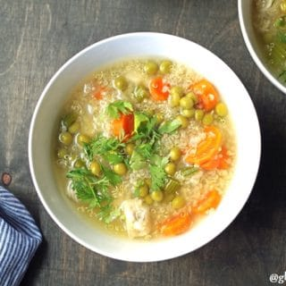 a close up of quinoa soup with vegetables in a white bowl
