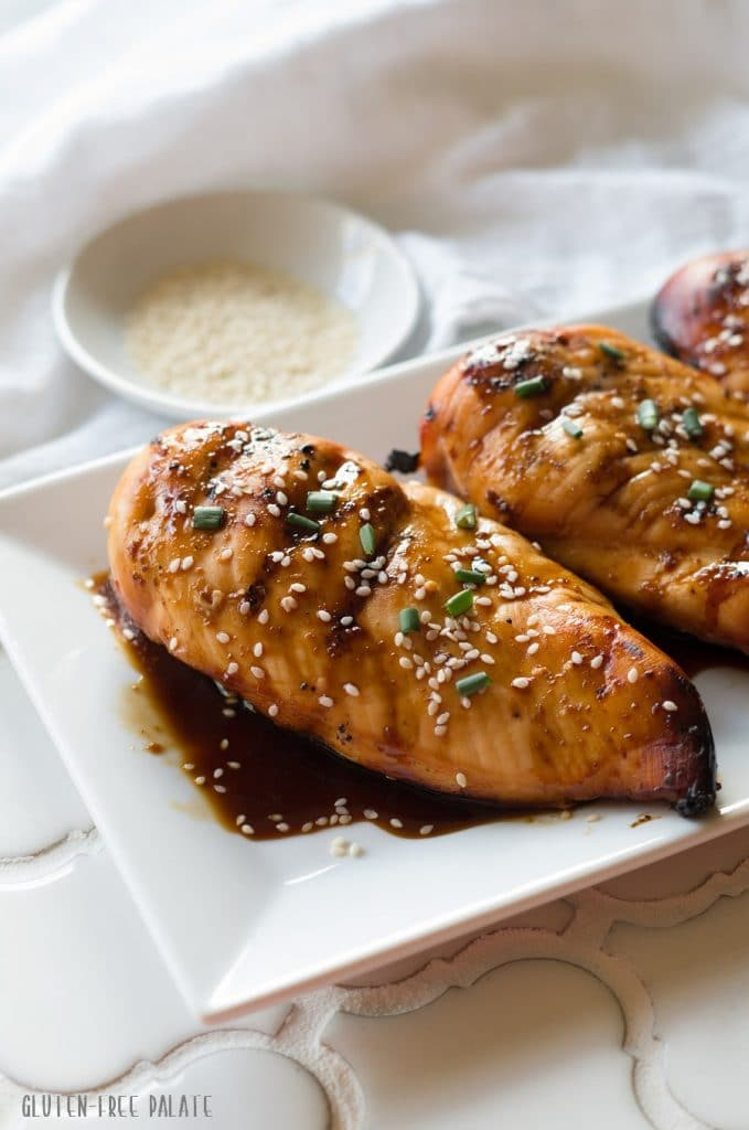 a side view of three Hawaiian chicken breasts on a white plate with sauce