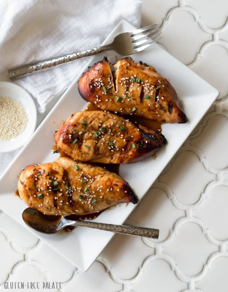 three Hawaiian chicken breasts on a white plate with sauce