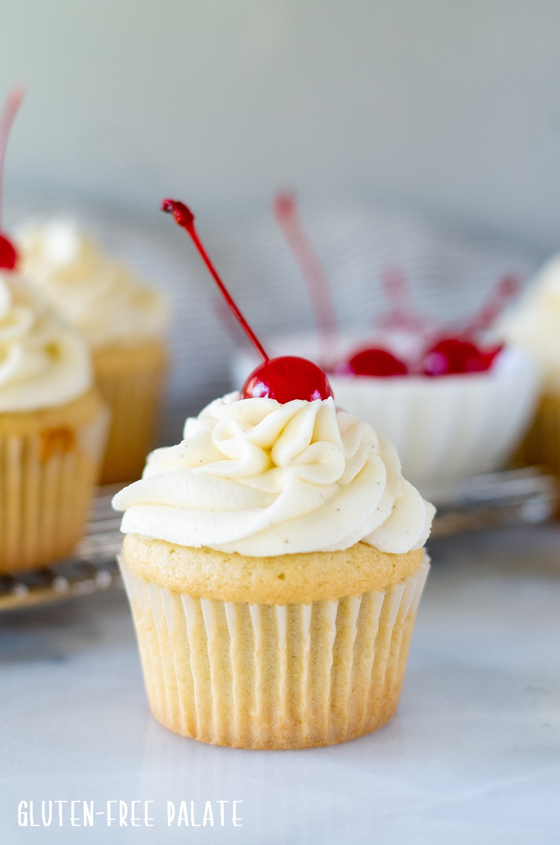 close up of a white Gluten Free Root Beer Cupcake topped with white frosting with a cherry on top and a bowl of red cherries in the background