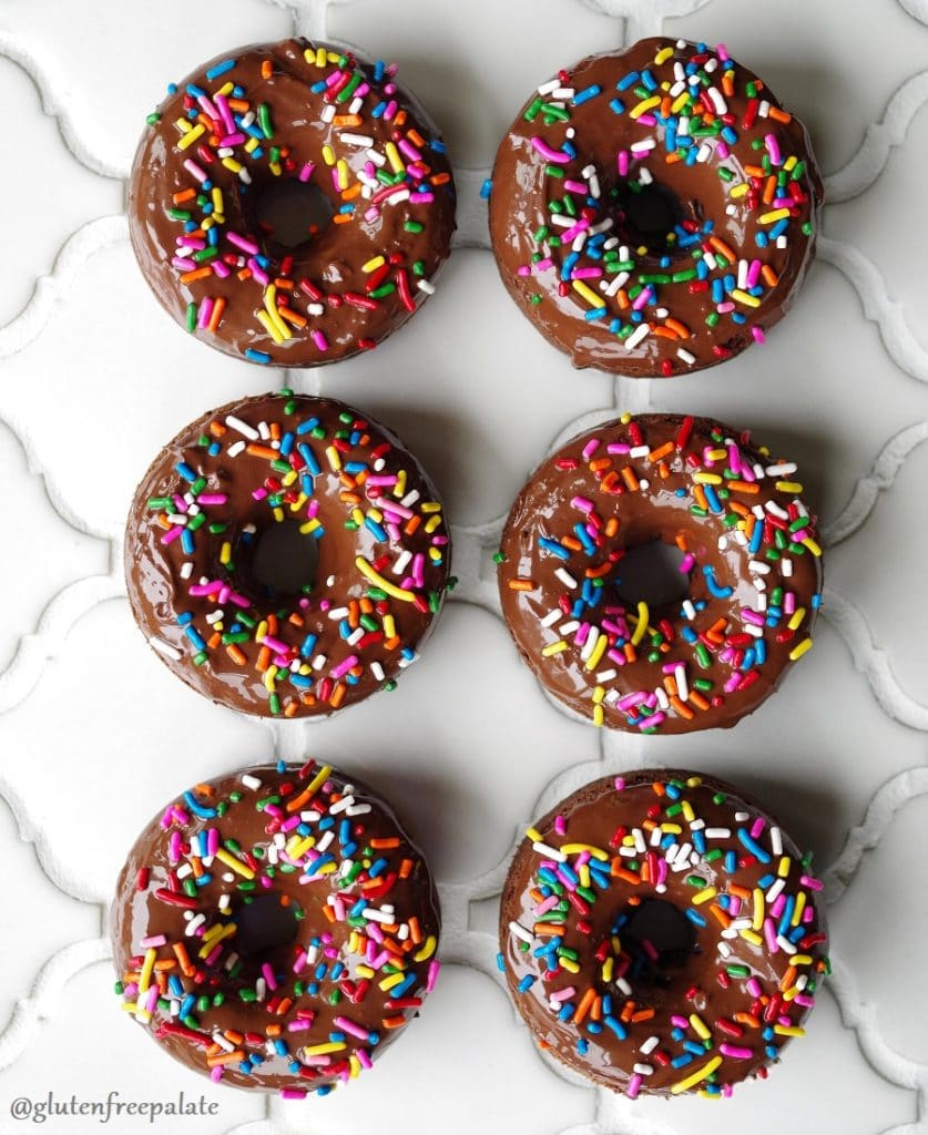 six chocolate cake donuts with chocolate glaze and colored sprinkels on top