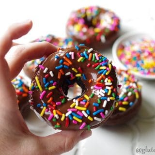 a close up of a hand holding a chocolate donut with colored sprinkles