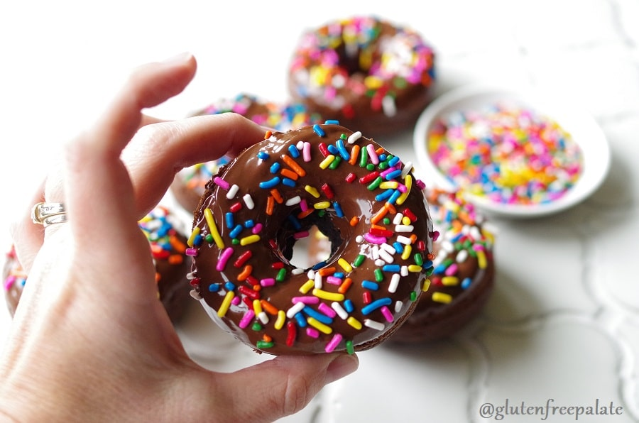 a hand holding a chocolate donut with colored sprinkles
