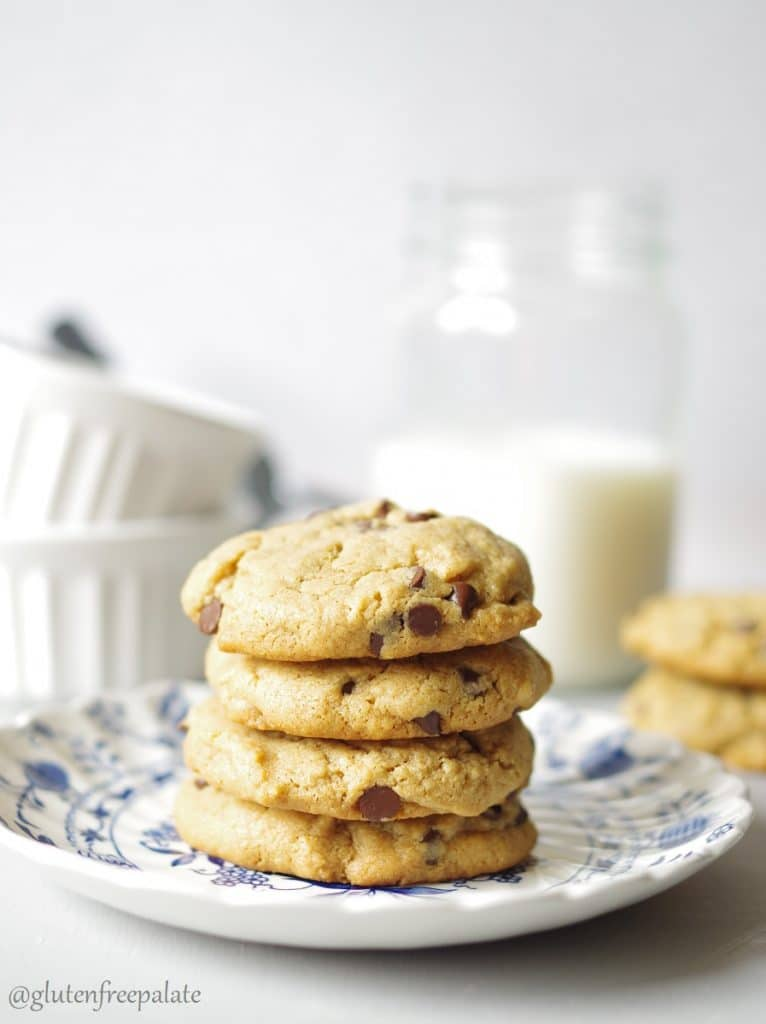 four gluten free peanut butter cookies with chocolate chips on a blue and white place with milk in the background