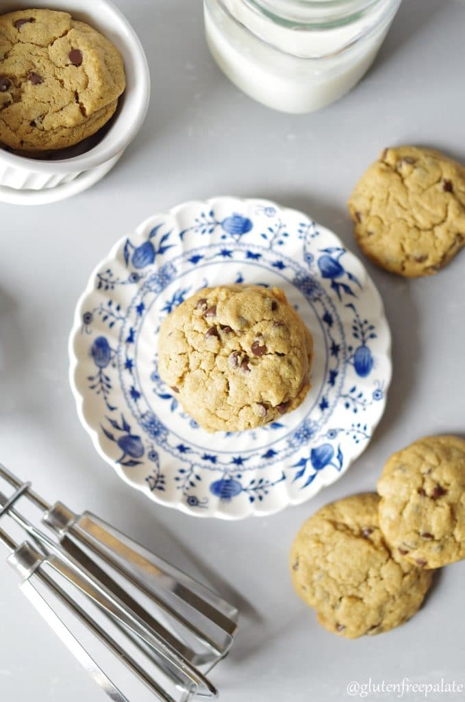 top down view of peanut butter cookies on a white and blue plate with three cookies around the plate and one cookie in a white ramekin