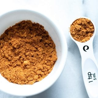 a close up of gluten free taco seasoning in a white bowl next to a measuring spoon with taco seasoning in it