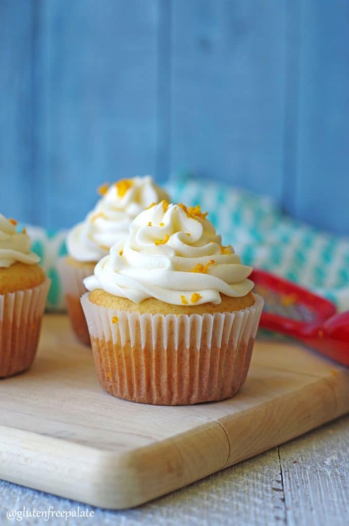 orange cupcakes with white frosting and orange zest on a wooden board
