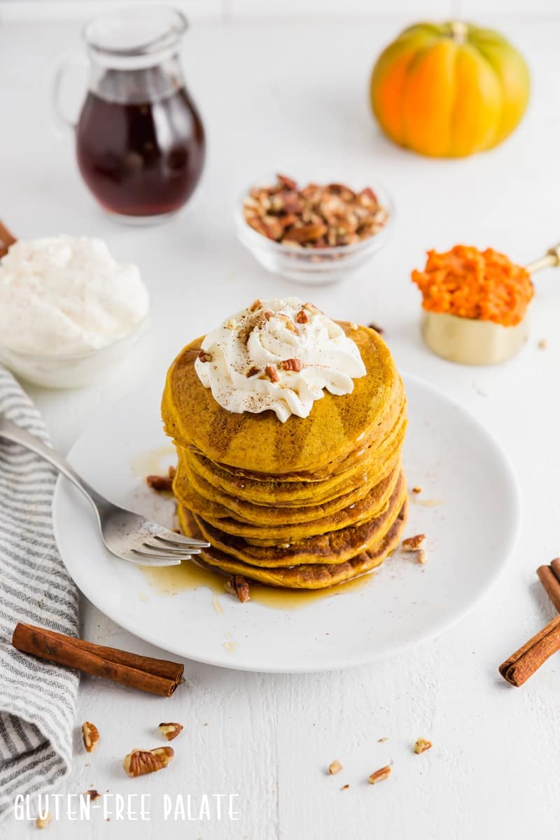a stack of gluten free pumpkin pancakes topped with whipped cream