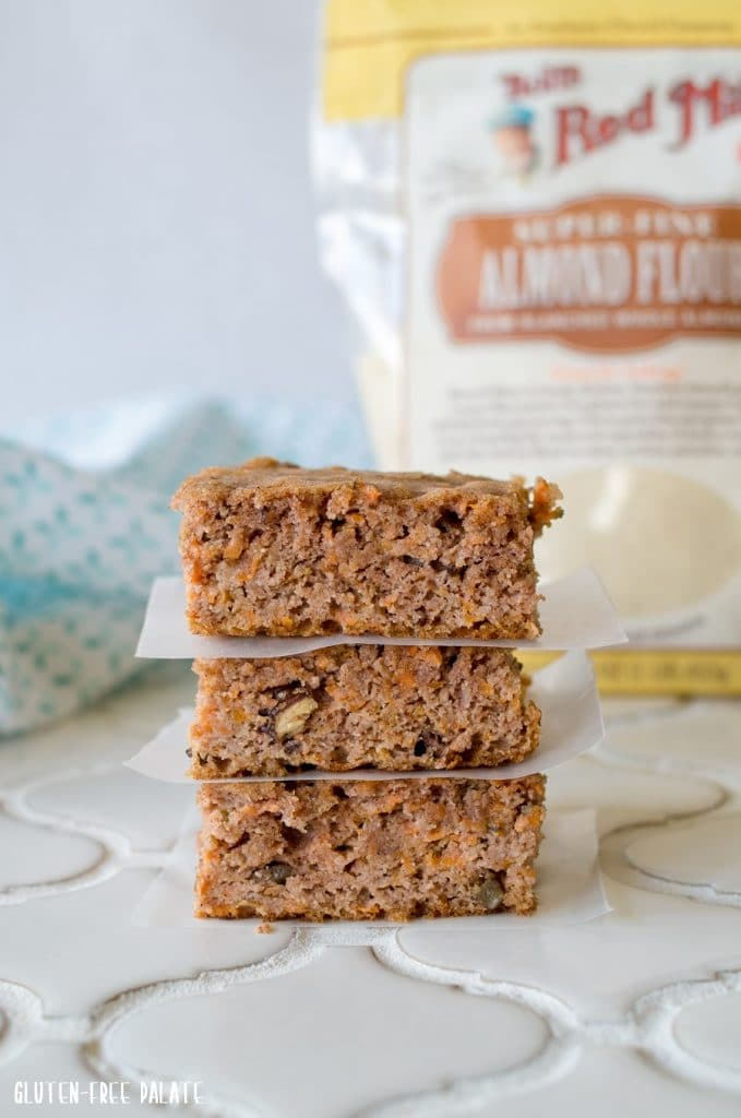 three Paleo Carrot Cake Bars stacked with parchment paper in between, a bag of almond flour in the background
