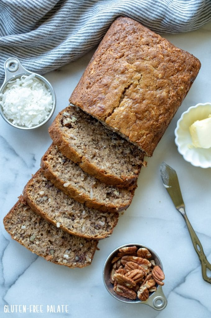 Gluten-Free Banana Bread sliced on marble slab next to a measuring cup of coconut and a measuring cup of pecans
