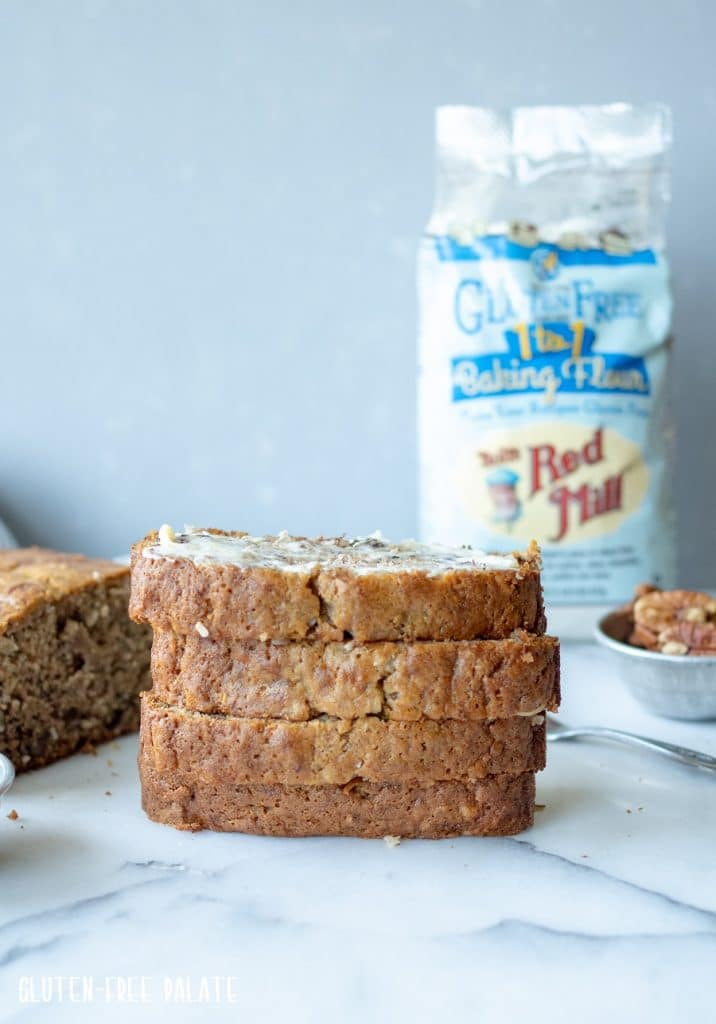 four slices of Banana Bread sliced on a plate with a bag of flour in the background