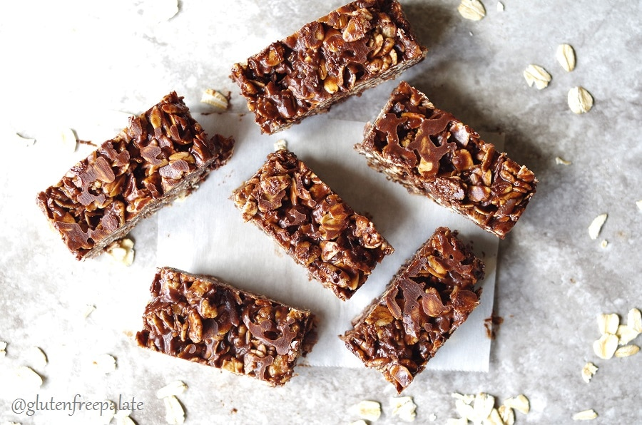 six chocolate oat bars with scattered oats around them