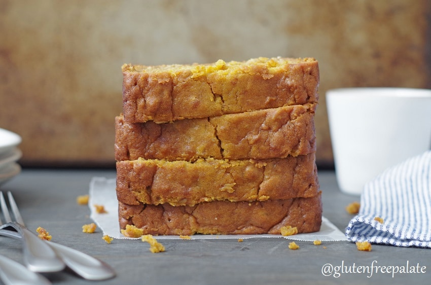 four slices of gluten-free pumpkin bread stacked, next to forks and a stripe napkin