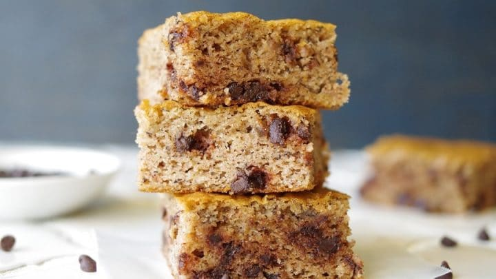 a close up of three paleo banana bars with chocolate chips stacked
