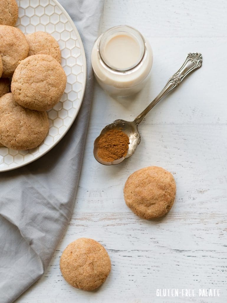two paleo snickerdoodle cookies next to a plate of cookies and a spoon of cinnamon