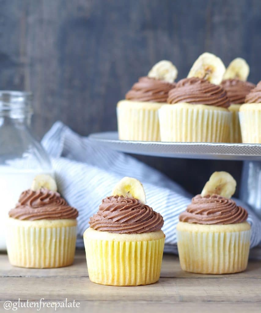 banana cupcakes topped with chocolate frosting and a banana chip