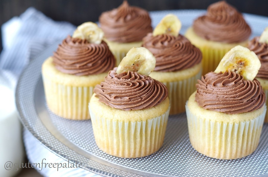 a close up of banana cupcakes topped with chocolate frosting and a banana chip on a cake stand