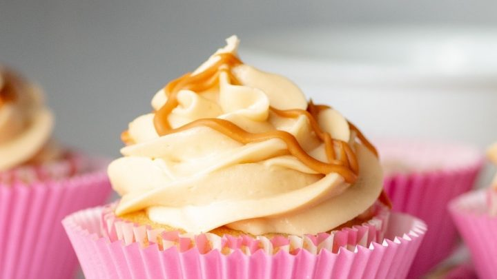 a close up of a Gluten-Free Butterscotch Cupcake in a pink peper liner, topped with buttercream frosting and a drizzle of butterscotch