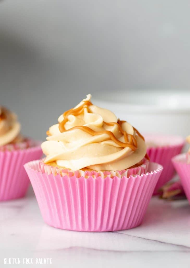 a Gluten-Free Butterscotch Cupcake in a pink peper liner, topped with buttercream frosting and a drizzle of butterscotch