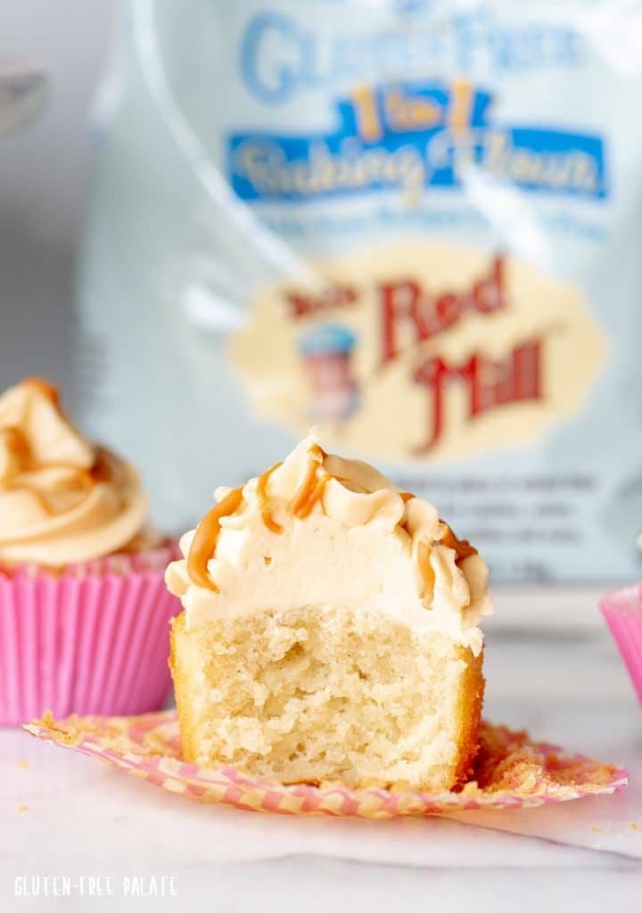 a Gluten-Free Butterscotch Cupcake cut in half, topped with buttercream frosting and a drizzle of butterscotch
