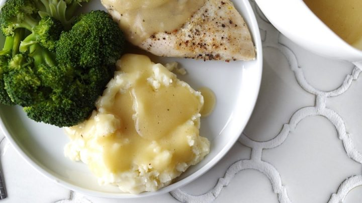 Gluten-Free Five Minute Gravy on chicken and potatoes on a plate with broccoli on a white plate