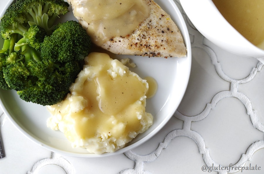 a close up of chicken and mashed potatoes with gluten free gravy on a white plate with broccoli