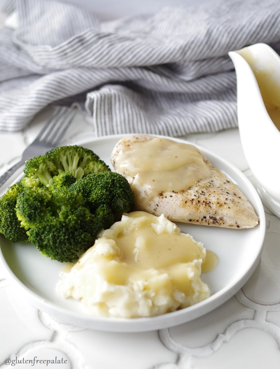 mashed potatoes and gravy, broccoli, and chicken with gravy on a white plate next to a gravy boar and a stripe towel