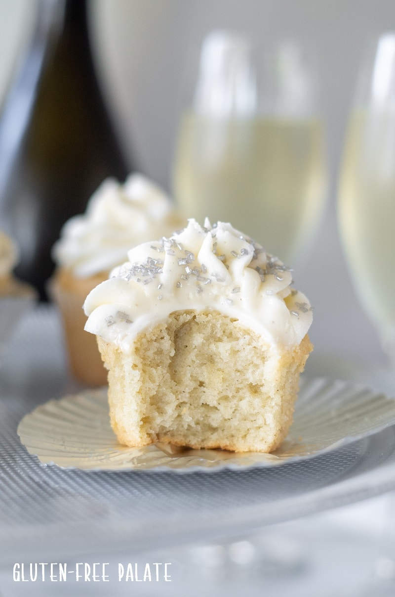 Gluten Free Champagne Cupcakes with silver sprinkles, with a bite out