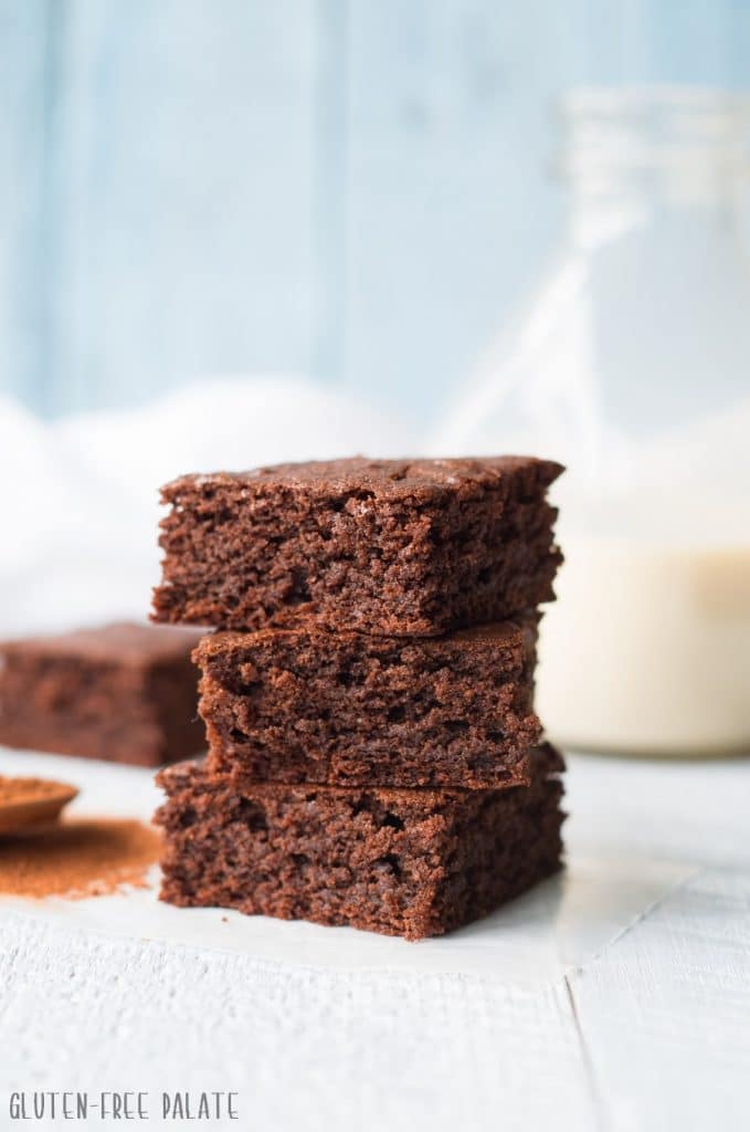 three chocolate gingerbread bars stacked in front of a jar of milk
