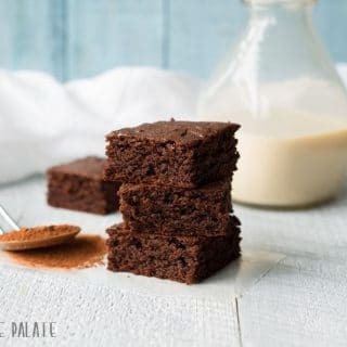 a close up of three chocolate gingerbread bars stacked in front of a jar of milk