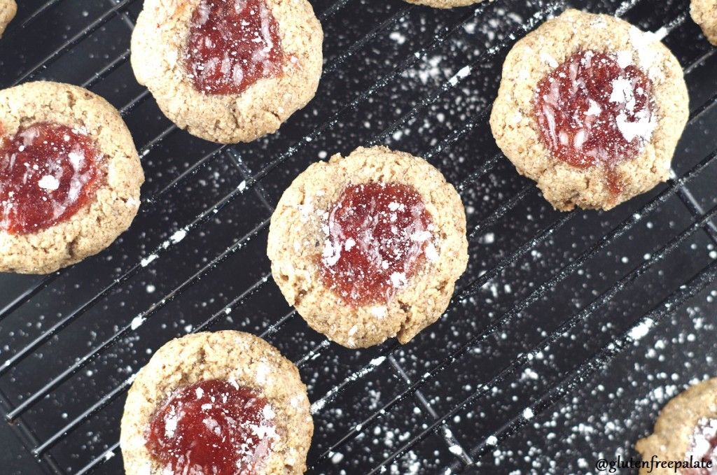 a top down view of paleo strawberry thumbprint cookies on a wire cooling rack
