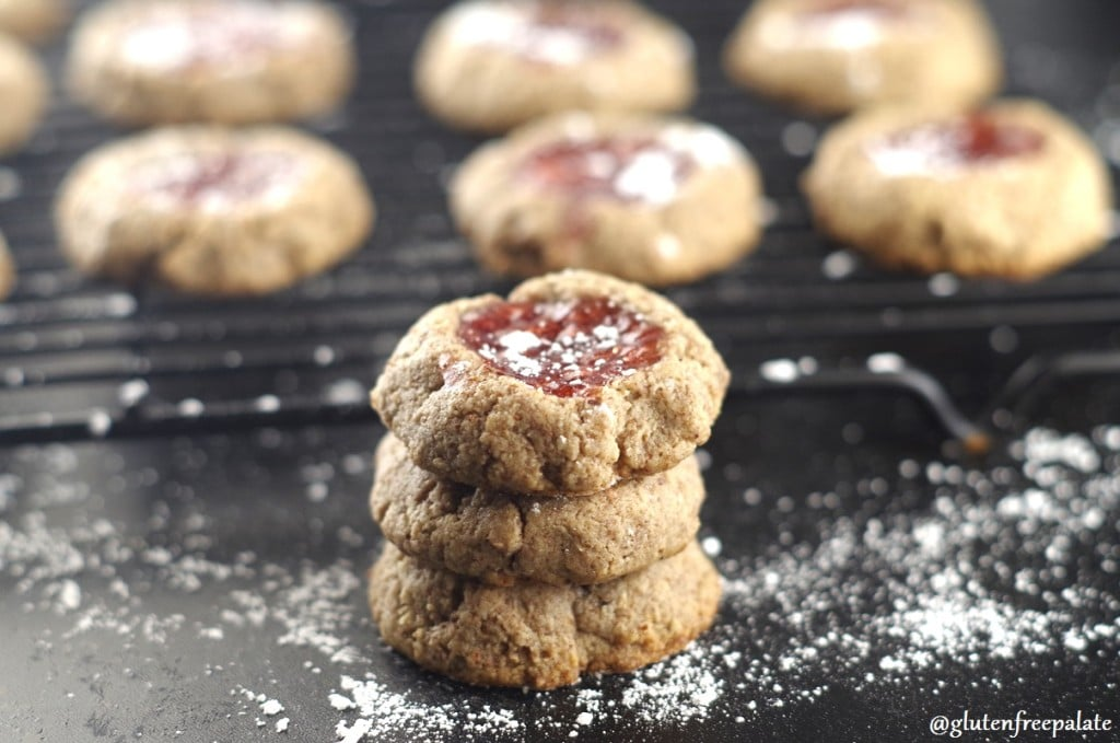 three strawberry thumbprint cookies sprinkled with powdered sugar stacked on a black backdrop with a cooking rack filled with cookies behind it