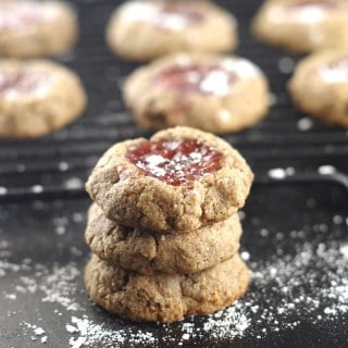 a close up of three paleo strawberry thumbprint cookies stacked in front of a wire cooling rack with cookies