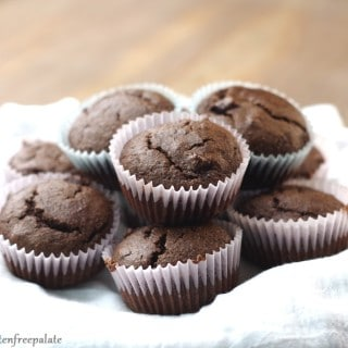 a close up of gluten free chocolate muffins arranged on a white towel