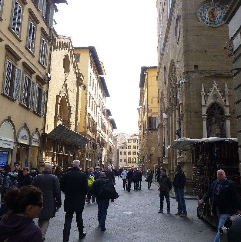 a walkway italy surrounded by buildings and busy with people